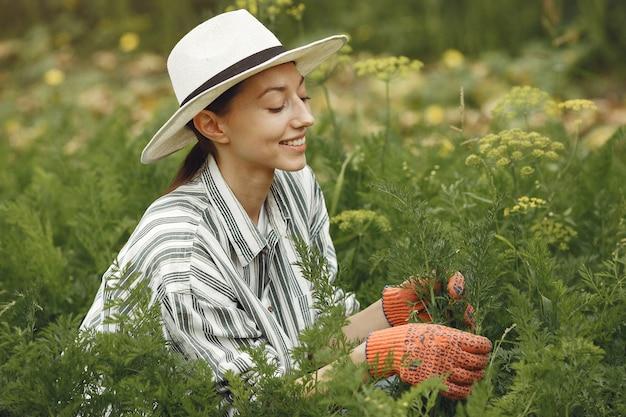 Jonge vrouw die voor planten zorgt. brunette in een hoed en handschoenen.