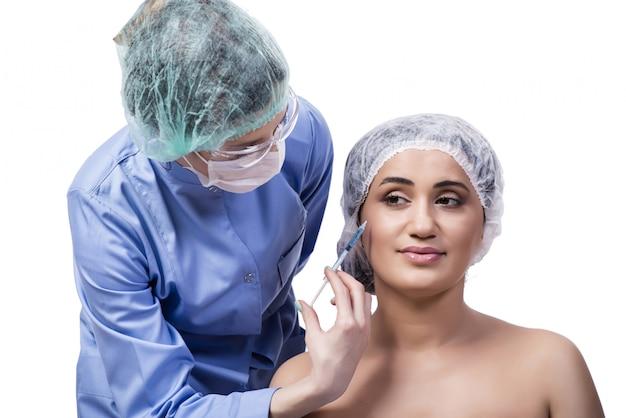 Jonge vrouw die voor plastische chirurgie voorbereidingen treft die op wit wordt geïsoleerd