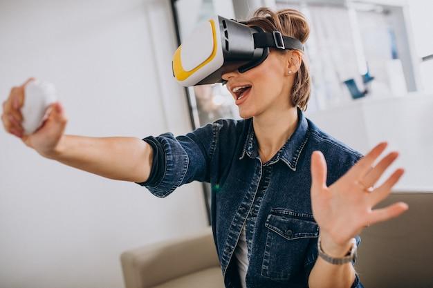 Jonge vrouw die vr-bril draagt en virtueel spel speelt dat ver gebruikt