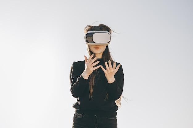 Jonge vrouw die vr-bril, hoofdtelefoon draagt, virtuele spellen speelt en video's in openlucht bekijkt