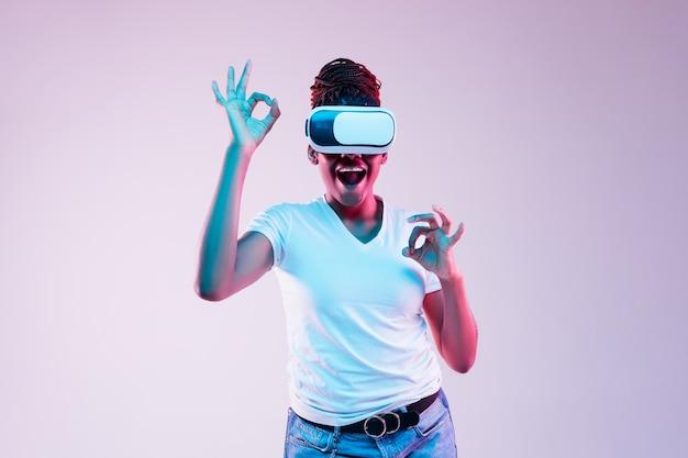 Jonge vrouw die vr-bril met neonlichten gebruikt