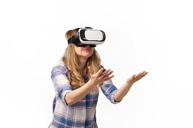 Jonge vrouw die vr-headset-apparaten, gadgets gebruikt die op witte studiomuur worden geïsoleerd