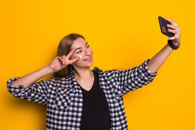 Jonge vrouw die vredesvingers toont en selfiefoto neemt die over gele muur wordt geïsoleerd
