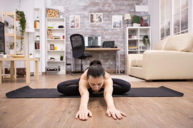 Jonge vrouw die vreedzaam mediteert op een mat zittend op een lotushouding die zich naar voren uitstrekt.