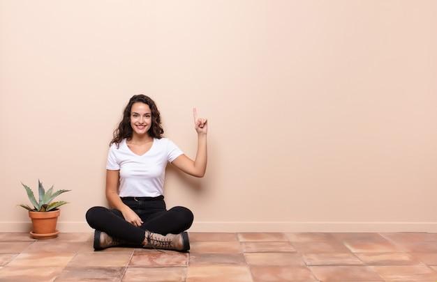 Jonge vrouw die vrolijk en gelukkig glimlacht, met één hand naar boven wijst om ruimte te kopiëren die op een terrasvloer zit