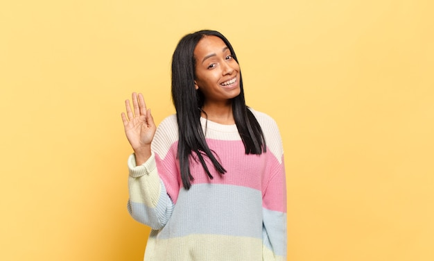 Jonge vrouw die vrolijk en opgewekt lacht, met de hand zwaait, je verwelkomt en begroet, of afscheid neemt