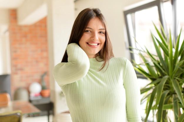 Jonge vrouw die vrolijk en vol vertrouwen lacht met een ongedwongen, gelukkige vriendelijke glimlach