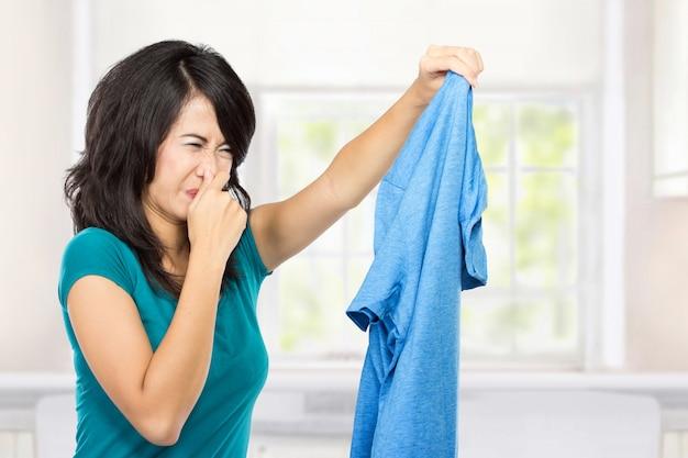 Jonge vrouw die vuile kleren houdt