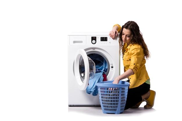 Jonge vrouw die vuile wasserij doet die op wit wordt geïsoleerd