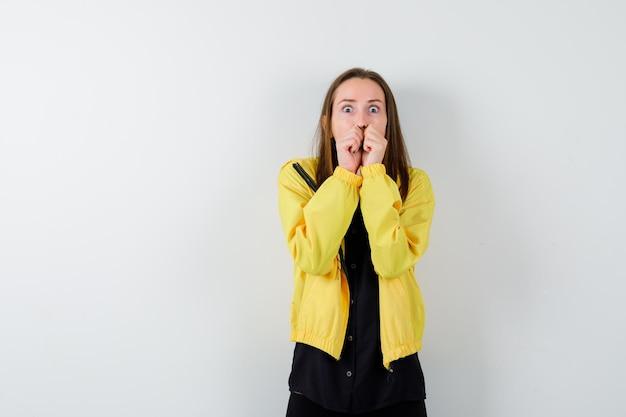 Jonge vrouw die vuisten bijt en er angstig uitziet
