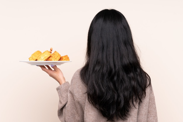 Jonge vrouw die wafels over geïsoleerde muur eet