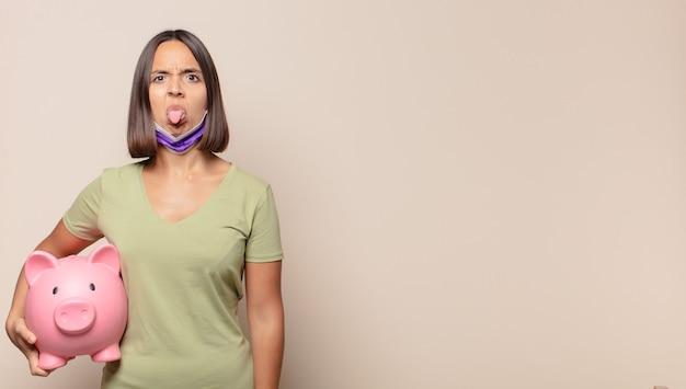 Jonge vrouw die walgt en geïrriteerd is, tong uitsteekt