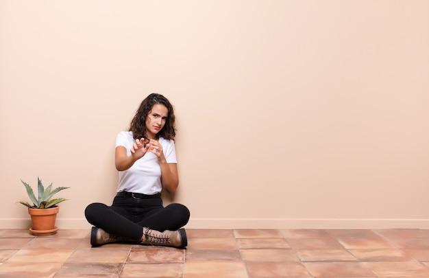 Jonge vrouw die walgt en misselijk is, zich terugtrekt voor iets smerigs, stinkende of stinkende, zegt bah zittend op een terrasvloer