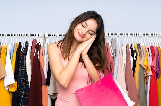 Jonge vrouw die wat kleren in een winkel koopt die slaapgebaar in dorable uitdrukking maken