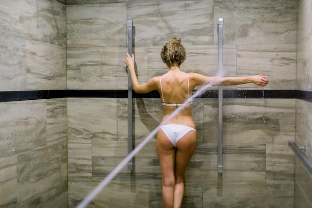 Jonge vrouw die watermassagebehandeling in speciale ruimte voor hoge drukmassage met sharko-douche in kuuroord hebben