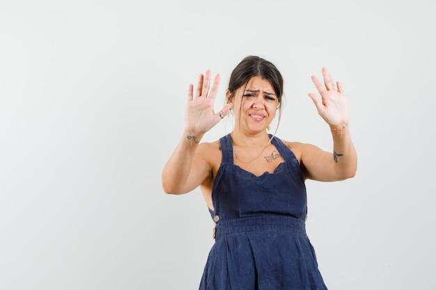 Jonge vrouw die weigeringsgebaar in kleding toont en geïrriteerd kijkt
