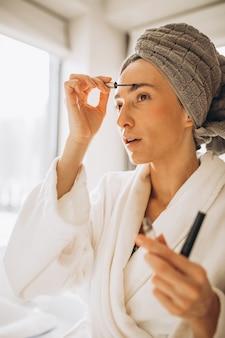 Jonge vrouw die wenkbrauwen borstelt en in de spiegel kijkt