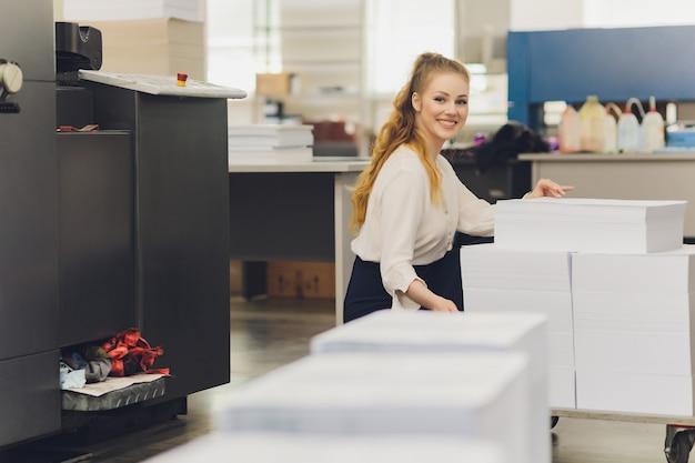 Jonge vrouw die werkt in de drukkerij. drukpers.