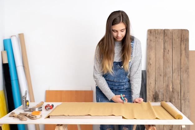 Jonge vrouw die werkt in een ambachtelijke werkplaats met verschillende gereedschappen en materialen