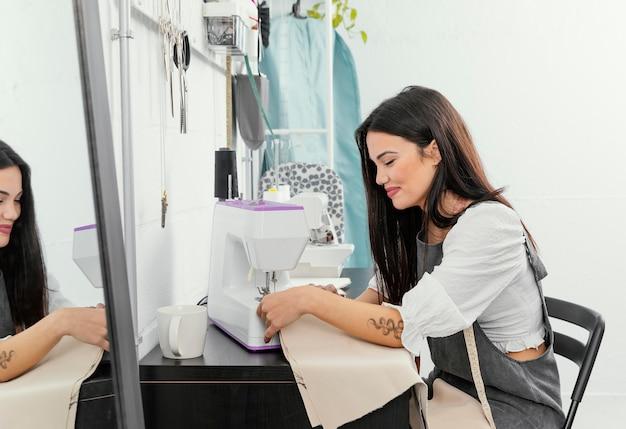 Jonge vrouw die werkt in haar workshop modevormgeving