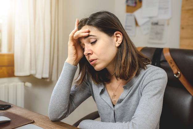 Jonge vrouw die werkt of studeert aan bureau moe en gestrest legt hand op het hoofd.