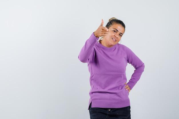 Jonge vrouw die wijst terwijl ze de hand op de taille houdt