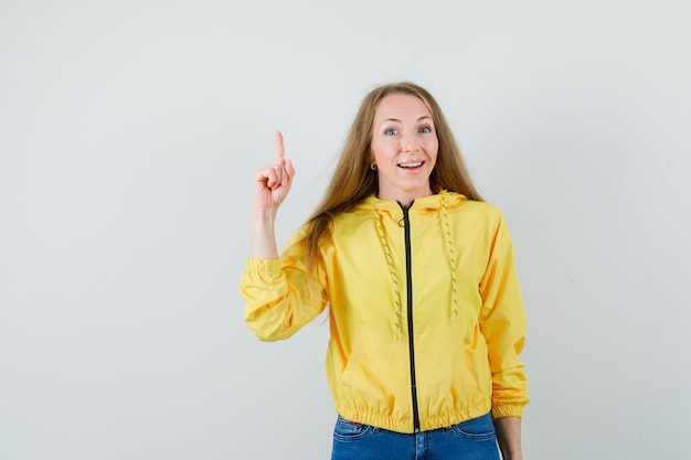 Jonge vrouw die wijsvinger in eureka-gebaar in geel bomberjack en blauwe jean opheft