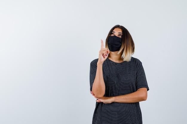 Jonge vrouw die wijsvinger in eureka-gebaar opheft, hand onder elleboog houdt, omhoog kijkt in zwarte jurk, zwart masker en er verstandig uitziet, vooraanzicht.
