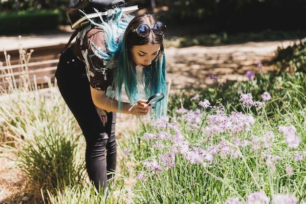 Jonge vrouw die wilde bloemen door vergrootglas kijkt