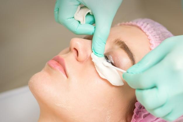 Jonge vrouw die wimperverwijderingsprocedure ontvangt en mascara verwijdert met een wattenstaafje en stok in een schoonheidssalon.