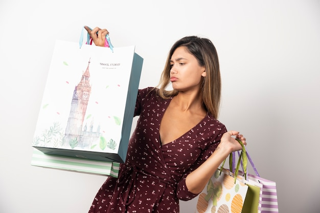 Jonge vrouw die winkeltassen op witte muur bekijkt.