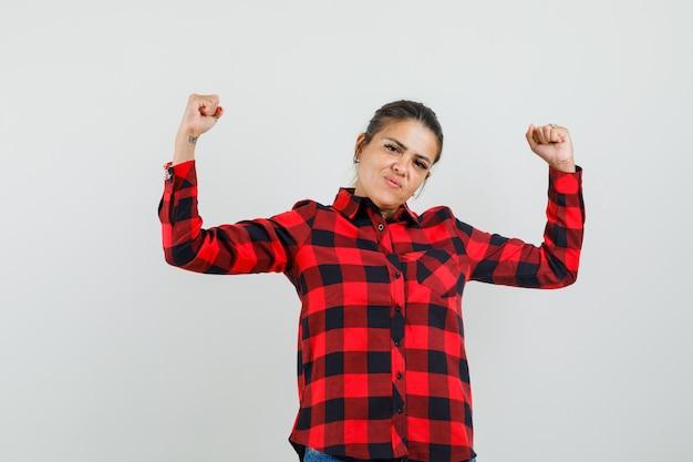 Jonge vrouw die winnaargebaar in gecontroleerd overhemd toont en gelukkig kijkt. vooraanzicht.