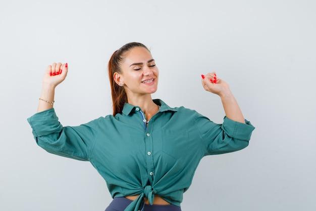 Jonge vrouw die winnaargebaar in groen overhemd toont en gelukkig kijkt. vooraanzicht.
