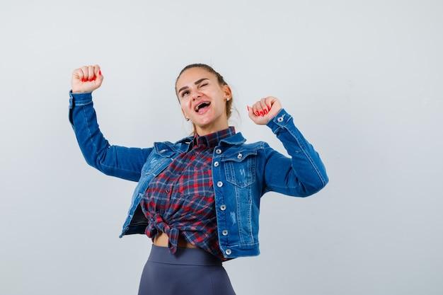 Jonge vrouw die winnaargebaar toont in geruit overhemd, jasje, broek en er zalig uitziet. vooraanzicht.