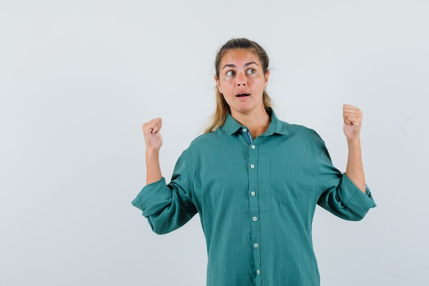 Jonge vrouw die winnaargebaar toont terwijl opzij in blauw overhemd kijkt en gelukkig kijkt