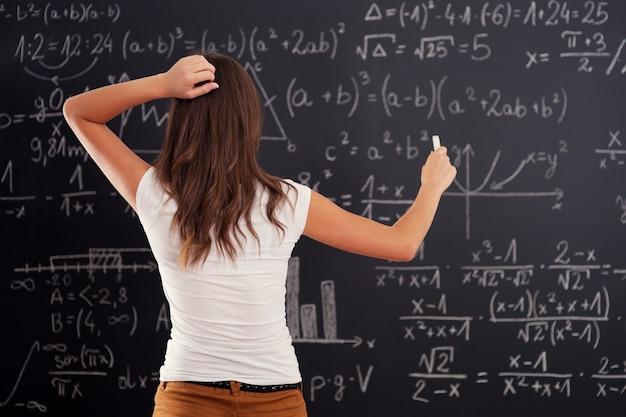 Jonge vrouw die wiskundeprobleem op bord bekijkt