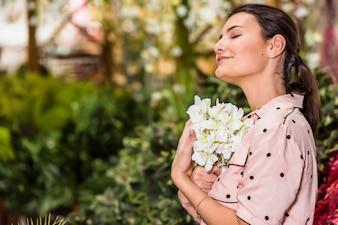 Jonge vrouw die witte bloem in groen huis houdt