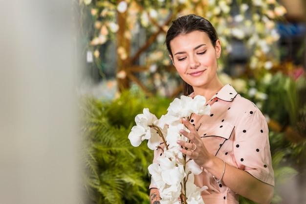 Jonge vrouw die witte bloemen bekijkt