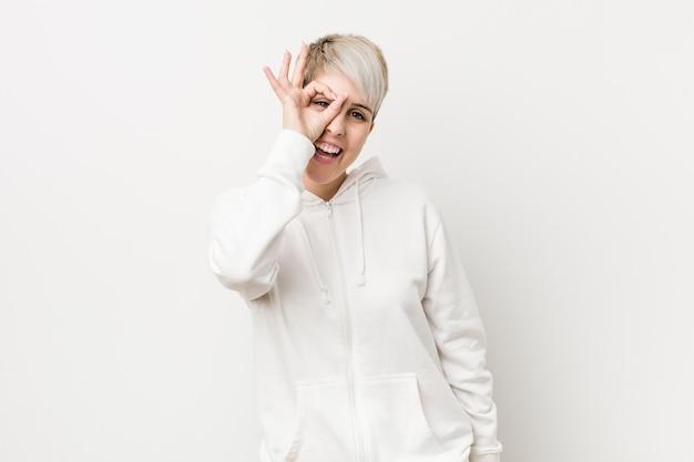 Jonge vrouw die witte opgewekte hoodie draagt houdend ok gebaar op oog