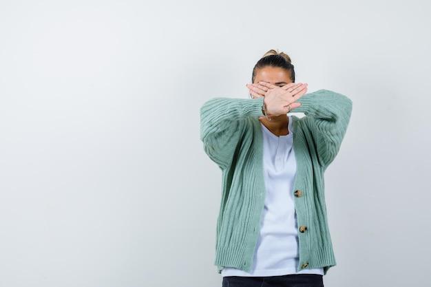 Jonge vrouw die x-gebaar toont in wit t-shirt en mintgroen vest en er serieus uitziet?