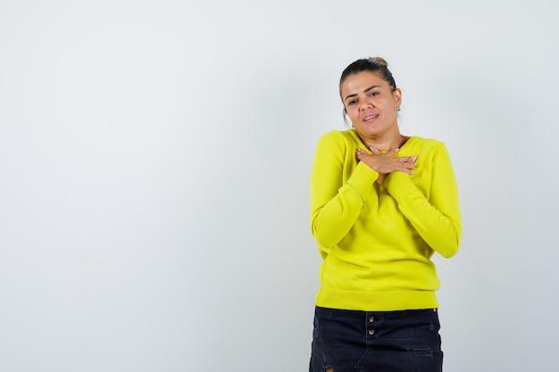 Jonge vrouw die x of beperkingsgebaar in gele trui en zwarte broek toont en er gelukkig uitziet