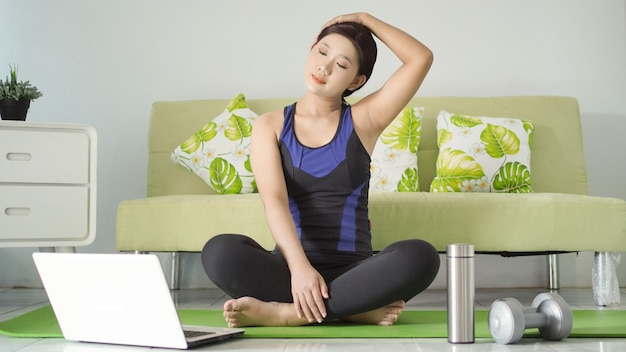 Jonge vrouw die yoga beoefent en bewegingen imiteert vanaf haar laptopscherm