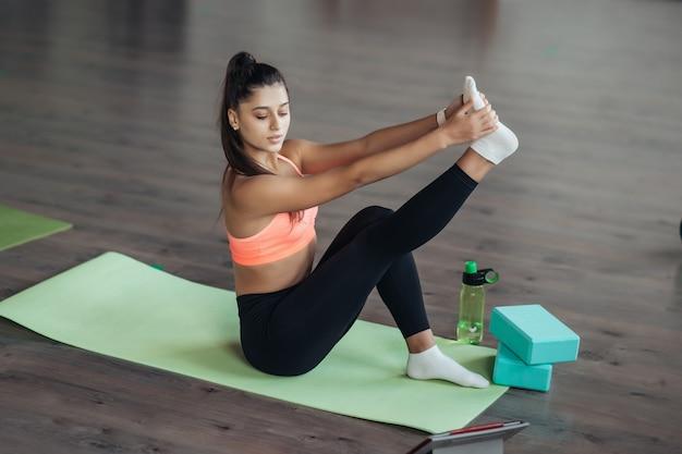 Jonge vrouw die yoga beoefent, houdt zich online bezig met de leraar.
