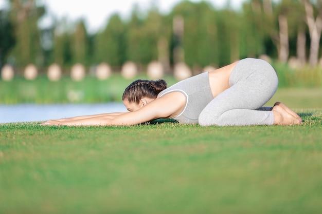 Jonge vrouw die yoga beoefent in het park