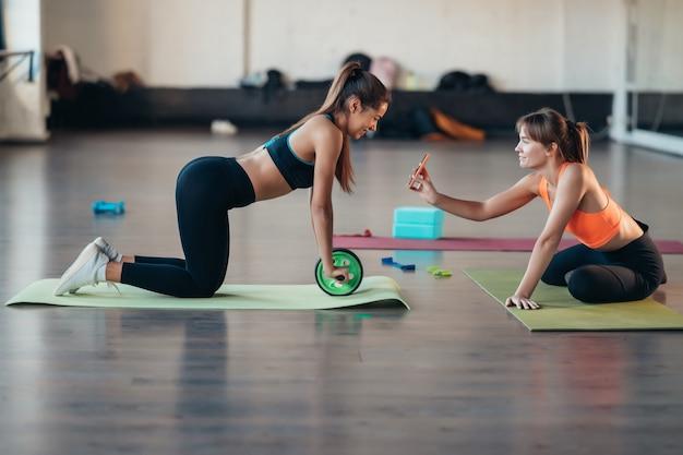 Jonge vrouw die yoga beoefent, is online bezig met de leraar.