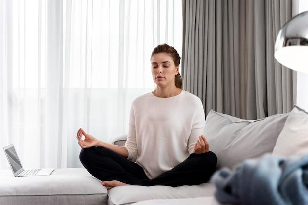 Jonge vrouw die yoga beoefent om te ontspannen