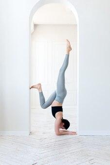 Jonge vrouw die yoga beoefent onder een witte boog binnenshuis