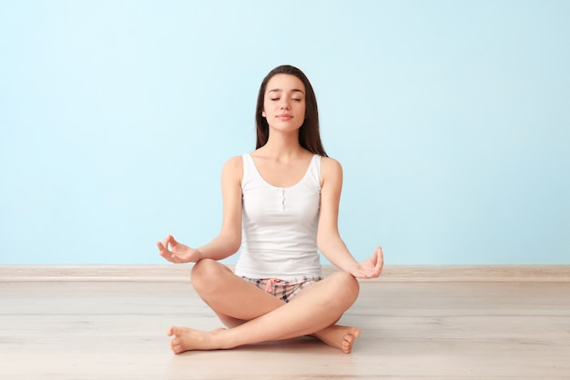 Jonge vrouw die yoga beoefent op de vloer