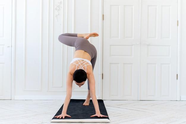 Jonge vrouw die yoga beoefent op een lichte achtergrond. gezond levensstijlconcept.