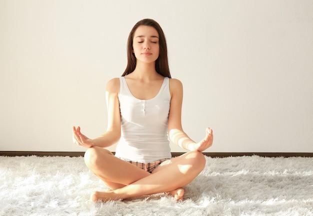 Jonge vrouw die yoga beoefent op harig tapijt